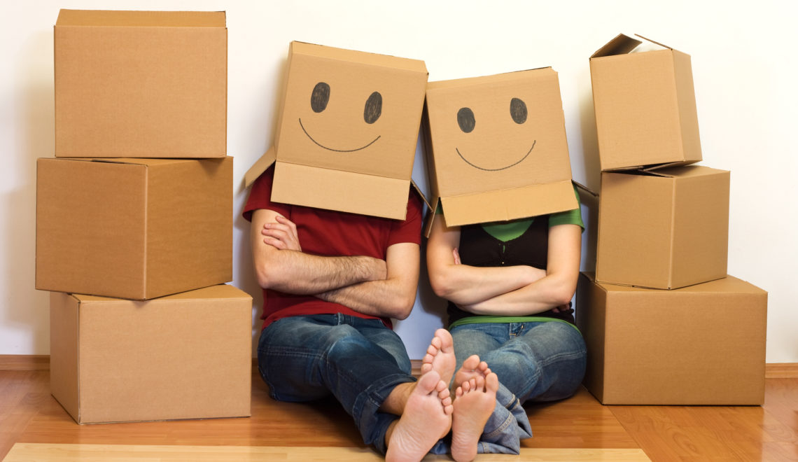 a couple sitting on the floor surrounded by moving boxes and wearing moving boxes on their heads with smiley faces drawn on