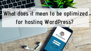 text reading what does it mean to be optimized for wordpress hosting against desk background with laptop, plant, headphones, and phone with wordpress sign up page open